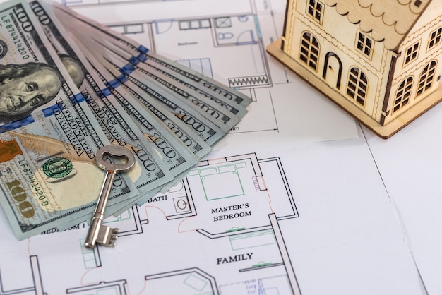 Modelo de casa de madeira com dólares e chave na planta