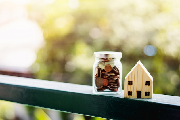 Modelo de casa de madeira com moedas de dinheiro no pote de vidro contra fundo desfocado natural ao ar livre, com espaço de cópia para negócios e finanças para o conceito de propriedade