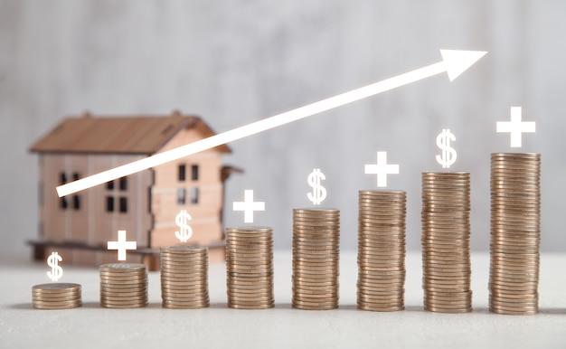 Modelo de casa de madeira com moedas na mesa branca com gráfico de lucro.