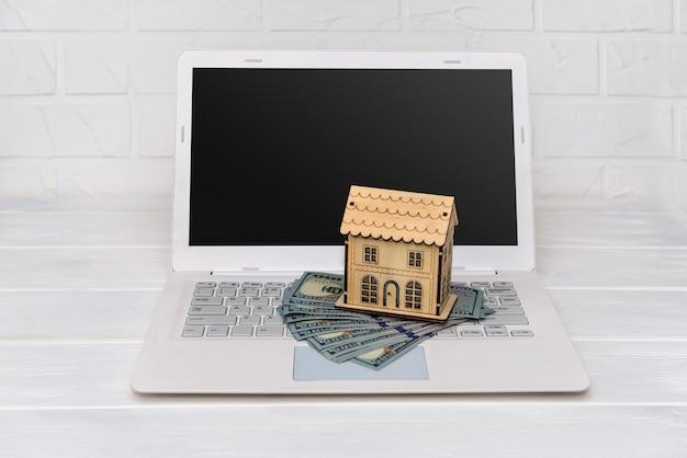 Modelo de casa de madeira com notas de dólar no teclado do laptop