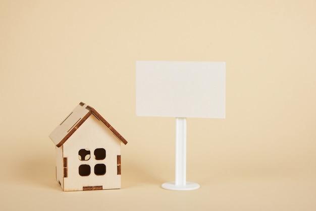 Modelo de casa de madeira e placa branca em branco sobre fundo bege cópia espaço conceito imobiliário
