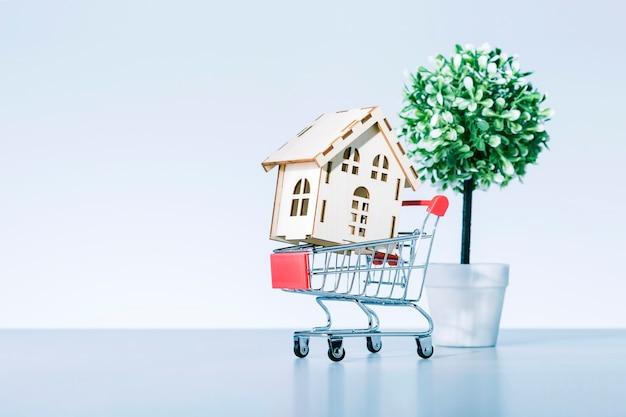 Modelo de casa de madeira no carrinho de compras e árvore no pote isoalted em fundo cinza, comprar o conceito de casa.