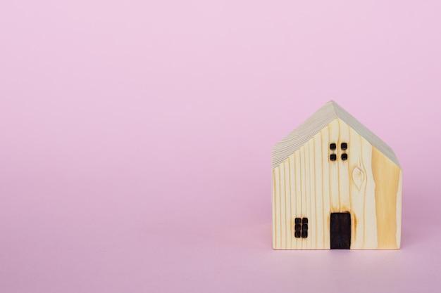 Modelo de casa de madeira no fundo rosa com espaço de cópia para o conceito de habitação