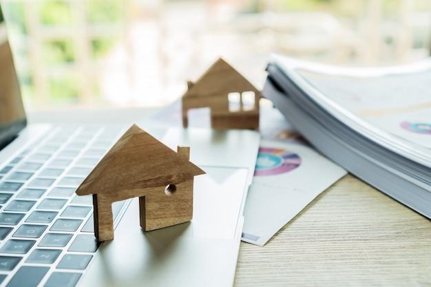 Modelo de casa de madeira no relatório de computador e gráfico, empréstimo de hipoteca de imóveis de propriedade ou conceito de investimento