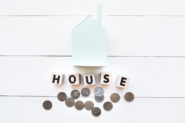 Modelo de casa de papel azul com blocos de madeira e moedas no pano de fundo branco de madeira