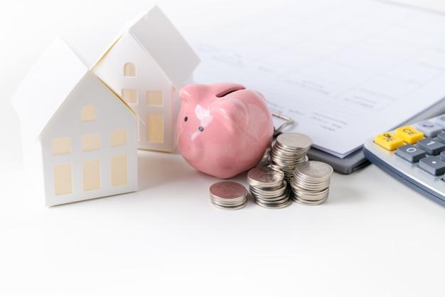 Modelo de casa de papel com moeda e cofrinho isolado