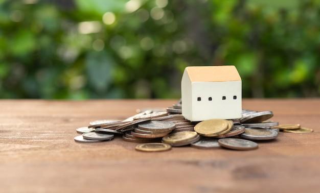 Modelo de casa definido na pilha de moedas de dinheiro na mesa de madeira com a natureza