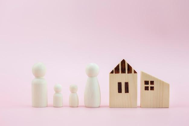 Modelo de casa diferente e família de pessoas em fundo rosa pastel