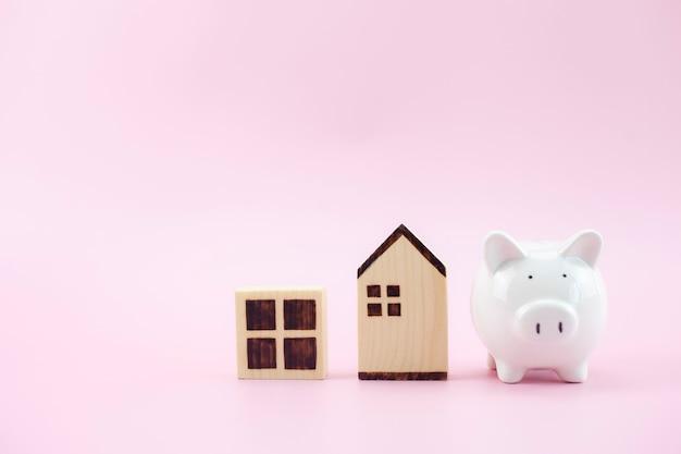 Modelo de casa diferente e porquinho branco sobre fundo rosa pastel