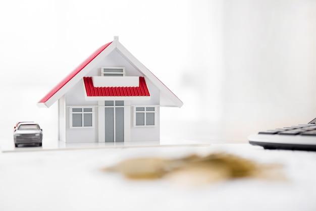 Modelo de casa e calculadora em cima da mesa com borrão pilha de moedas em primeiro plano