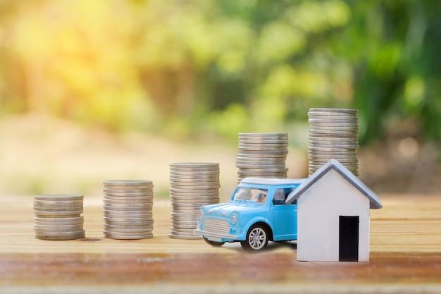 Modelo de casa e carro com moedas colocadas