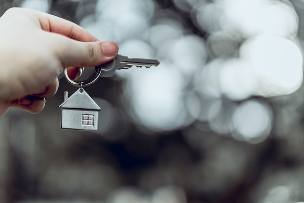 Modelo de casa e chave na mão do agente corretor de seguros em casa