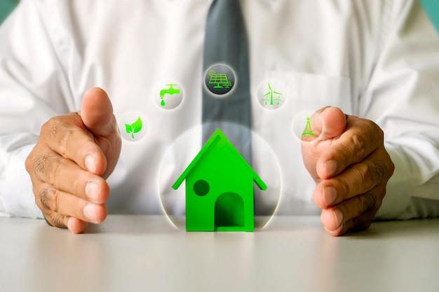 Modelo de casa e ícone de energia nas mãos do empresário masculino, casa de economia de energia e conceito de empréstimo à habitação.