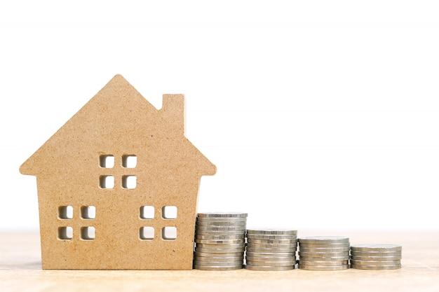 Modelo de casa e pilha de moedas na mesa para finanças e conceito bancário