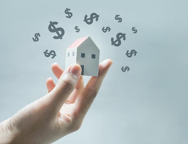 Modelo de casa em mãos humanas com o ícone de dólar. economiza dinheiro e conceito imobiliário