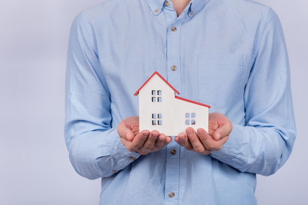 Modelo de casa em mãos masculinas. compra de casa, conceito de hipoteca