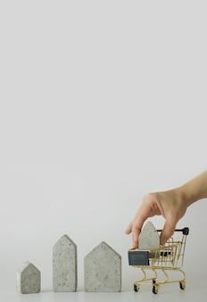 Modelo de casa em mini carrinho de compras em fundo branco. compre uma casa. conceito de escada de propriedade, hipoteca e investimento imobiliário. espaço livre para texto, cópia espaço, layout moderno.