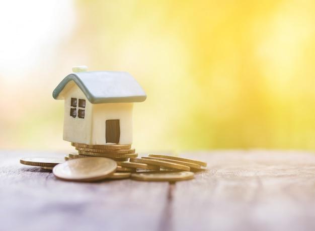 Modelo de casa em moedas economizando para financiamento de fundo de hipoteca de investimento de conceito e empréstimo à taxa de juros