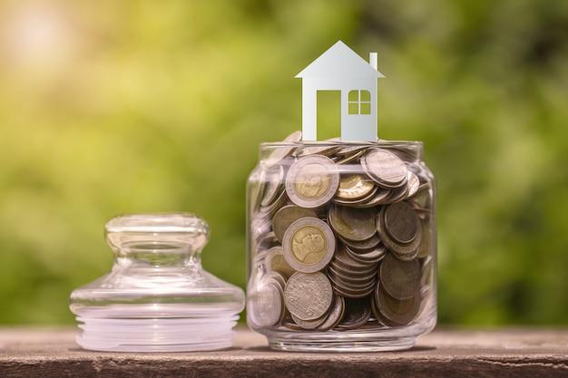 Modelo de casa em moedas em frasco de vidro