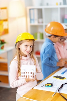Modelo de casa. linda garota com um capacete segurando uma pequena maquete de casa em pé perto de colegas de classe