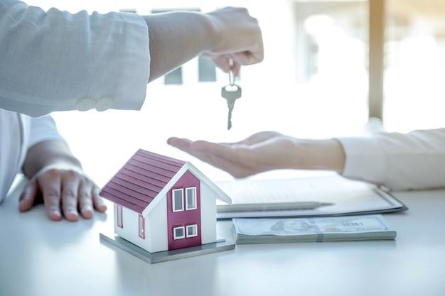 Modelo de casa mão de agente imobiliário detém as chaves e explica o contrato de negócios