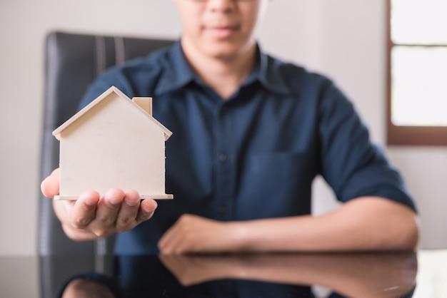 Modelo de casa na mão para finanças e banca, conceito de hipoteca de compra de casa