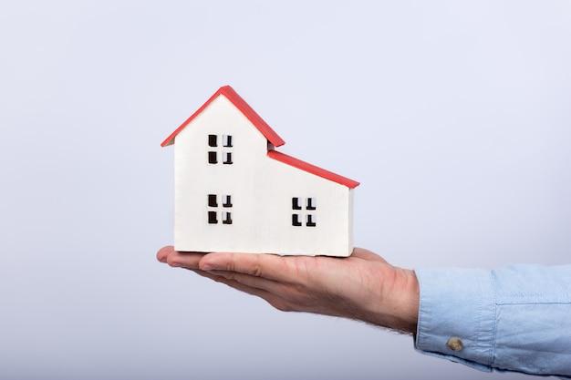 Modelo de casa na palma da mão sobre fundo branco. compre o conceito de casa própria