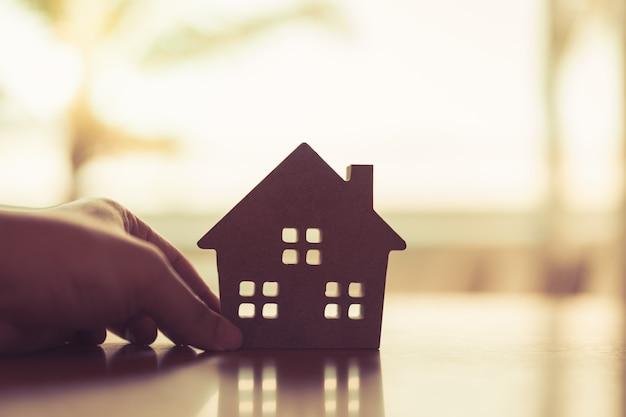 Modelo de casa nos agentes do corretor de seguros em casa, mão ou pessoa do vendedor.