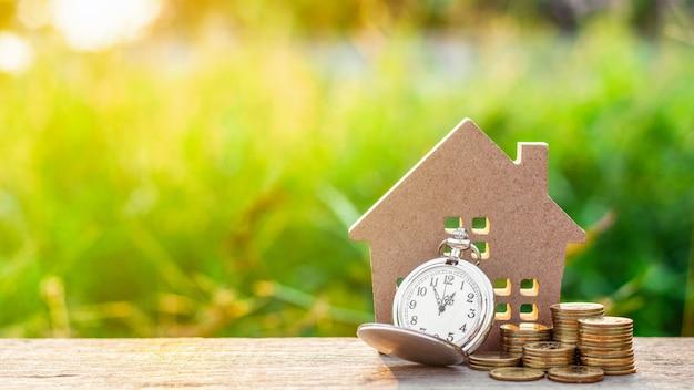 Modelo de casa pequena e um relógio com pilha de moedas de ouro