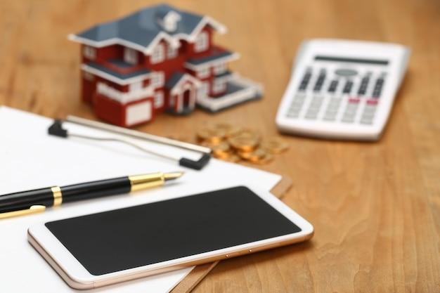 Modelo de casa, smartphone, calculadora e moedas de ouro na mesa de madeira