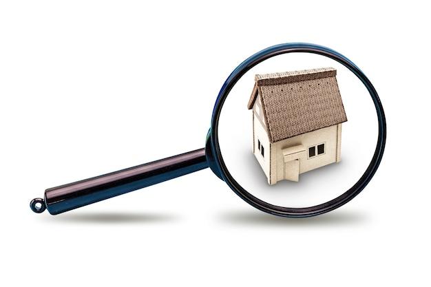 Modelo de casa sob uma lupa em um fundo branco e isolado. conceito de publicidade imobiliária. comprando, vendendo, alugando uma casa. hipoteca. copie o espaço.