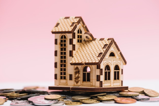 Modelo de casa sobre moedas na frente de fundo rosa