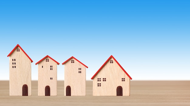 Modelo de casas de madeira em uma mesa de madeira sobre fundo azul