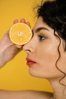 Modelo de close-up posando com rodela de limão