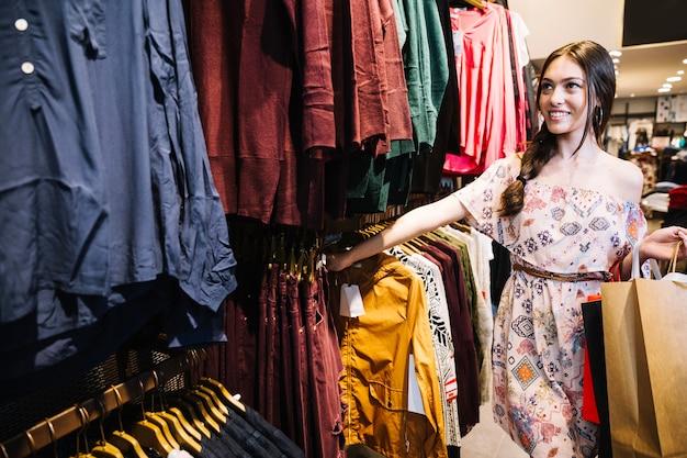 Modelo de conteúdo escolhendo roupas na loja