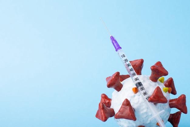 Modelo de coronavírus e uma seringa com vacina contra fundo azul