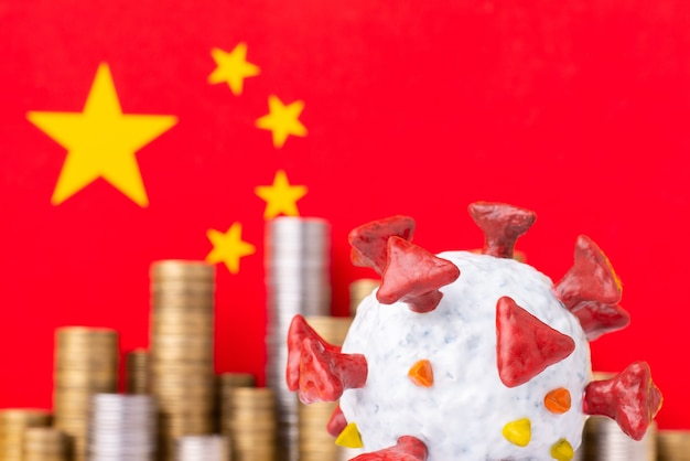 Modelo de coronavírus perto da bandeira da china e pilhas de moedas no
