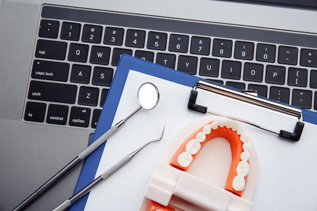 Modelo de dente saudável com ferramenta odontológica na mesa branca no consultório do dentista. conceito de higiene dentária