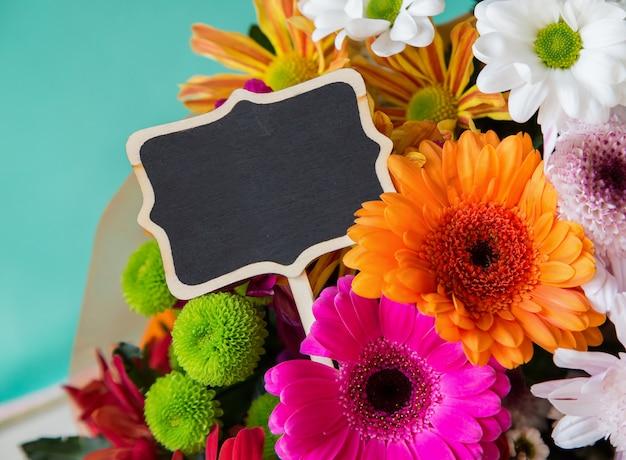 Modelo de design de texto com sinal de lousa e flores frescas coloridas