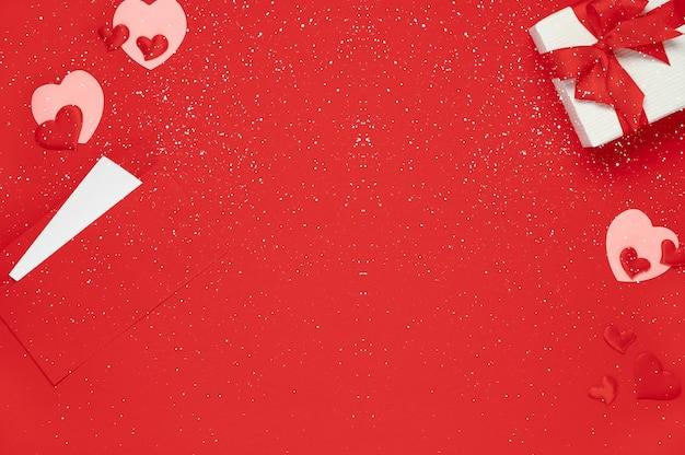 Modelo de dia dos namorados. vista superior da caixa de presente e corações de fundo vermelho com flocos de neve. cartão postal plano