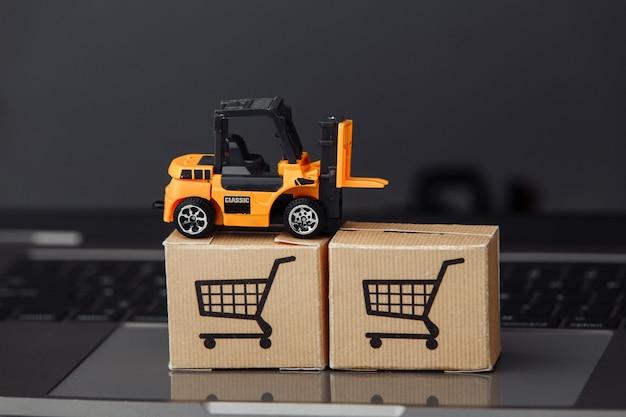 Modelo de empilhadeira em caixas de papelão em um laptop. serviços de correio e conceito de entrega