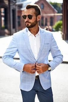 Modelo de empresário de moda bonito vestido elegante terno azul posando na rua