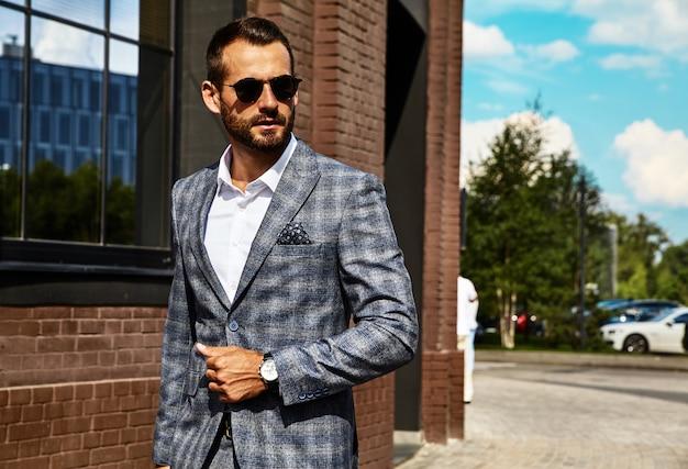 Modelo de empresário de moda bonito vestido elegante terno xadrez posando na rua