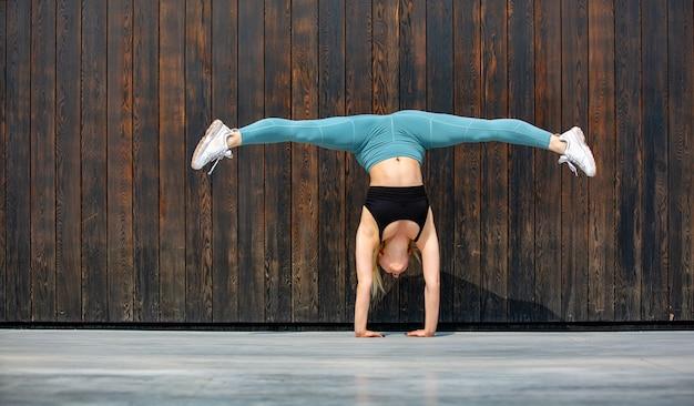 Modelo de esportes jovem europeu posando ao ar livre ao longo da parede de madeira, correndo, pulando, correndo, alongamento, vestindo no esporte fecha, tênis e top preto