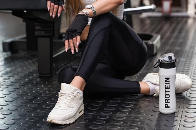 Modelo de fitness atraente sentado com bebida protéica na vista da parte inferior do ginásio moderno