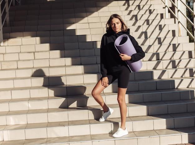 Modelo de fitness de beleza atraente posando ao sol da manhã no fundo das escadas
