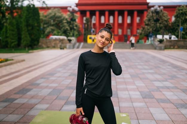 Modelo de fitness em roupas esportivas posando na rua da cidade