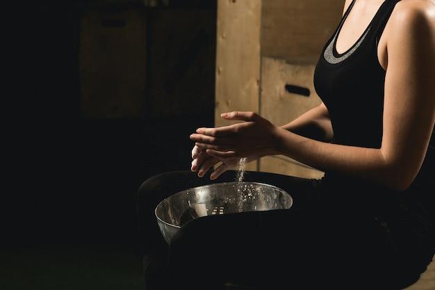 Modelo de fitness feminino batendo palmas de mãos com pó de talco