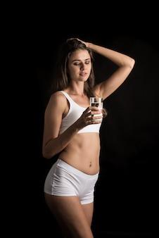 Modelo de fitness feminino segurando um copo de água