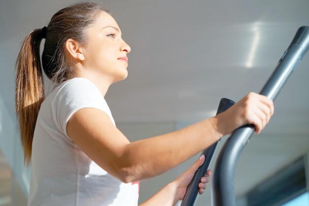 Modelo de fitness jovem atraente é executado em uma esteira, está envolvido no clube de esporte fitness.